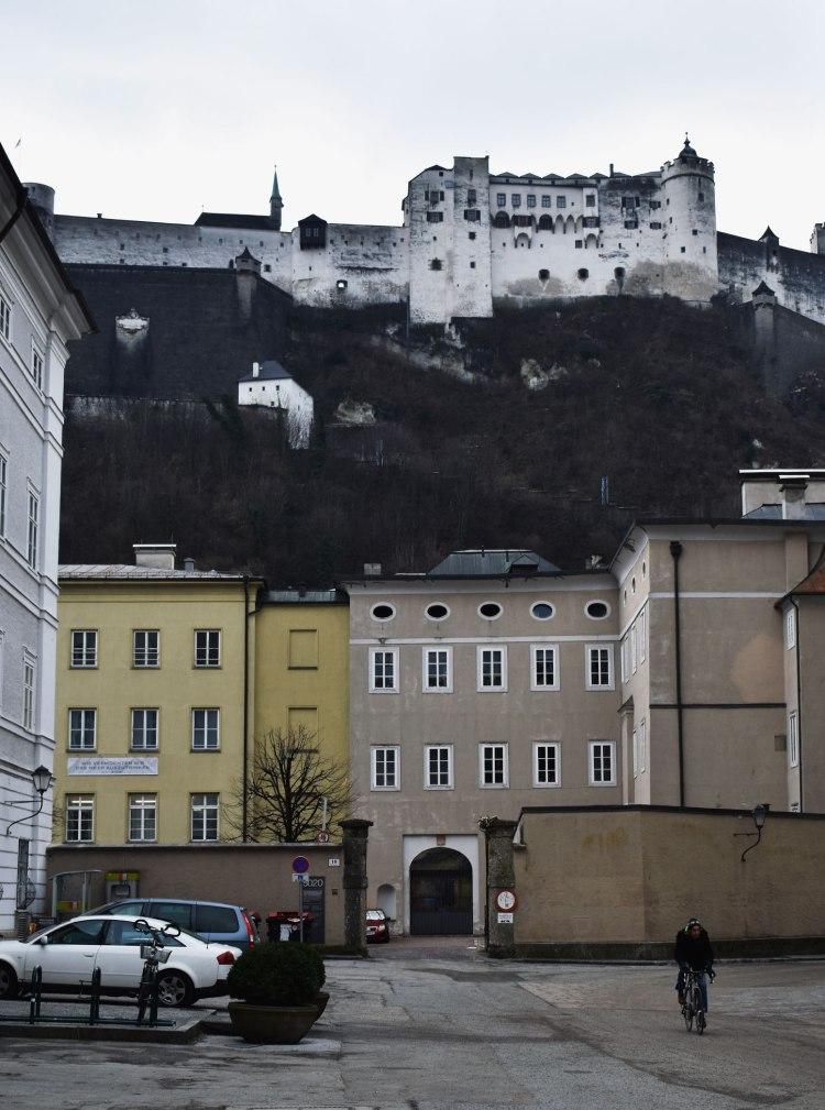 A cyclist rides beneath Fortress Hohensalzburg